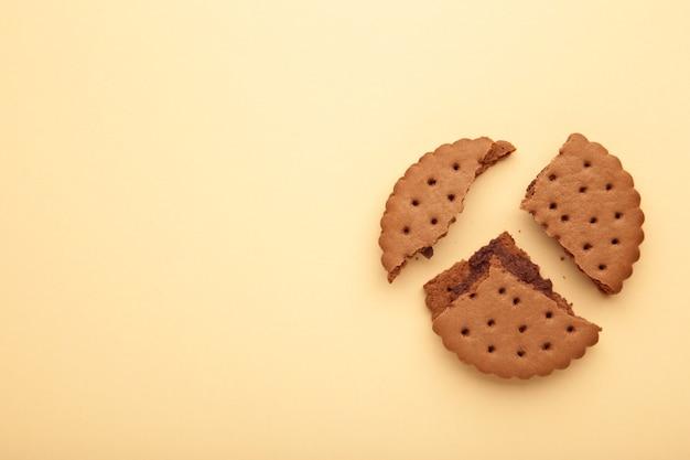 Chocolate chip cookie broken on beige background.top view.
