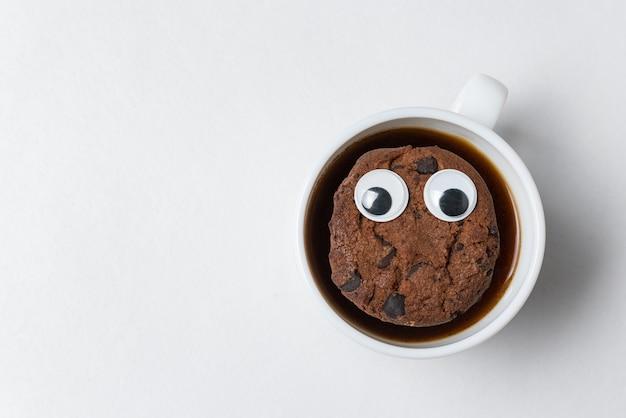 一杯のお茶にチョコレートチップクッキーのキャラクターが浮かんでいます。白い壁にクッキーとコーヒーカップ。上面図