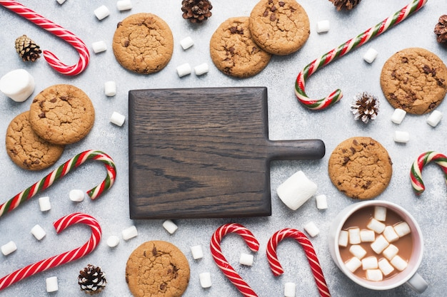 The chocolate chip cookie, christmas cane caramel cup cocoa and marshmallow cones decorations on a gray . copyspace frame.