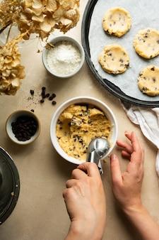 チョコレートチップクッキーの調理プロセス。女性の手ホールドアイスクリームスクープスプーン。フラットレイ。
