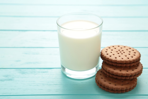 Chocolate chip cookie and glass of milk on blue wooden background. top view.