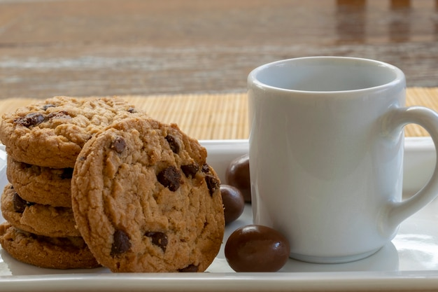 Chocolate chip cookie and white cup