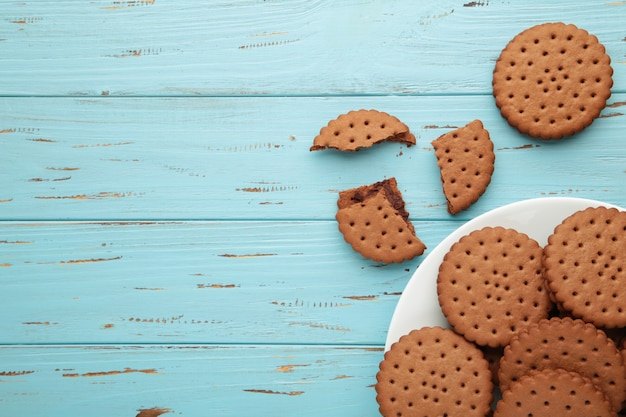 Chocolate chip cookie on white plate on blue wooden background. top view.