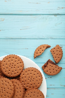 Chocolate chip cookie on white plate on blue wooden background. vertical photo.