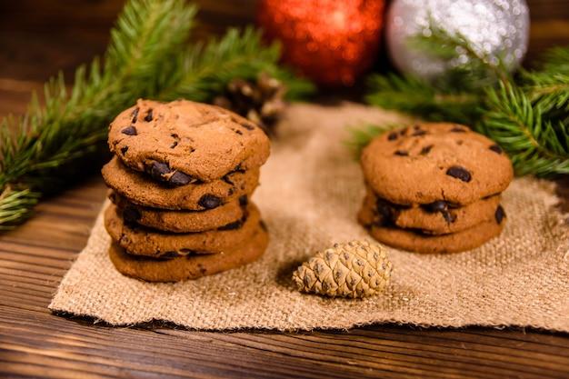 木製のテーブルにチョコレートチップクッキーとクリスマスの飾り