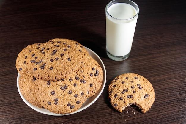 나무 테이블에 초콜릿 칩 쿠키와 우유 한 잔