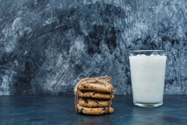 Шоколадное печенье и молоко на темно-синем мраморном фоне. крупный план.