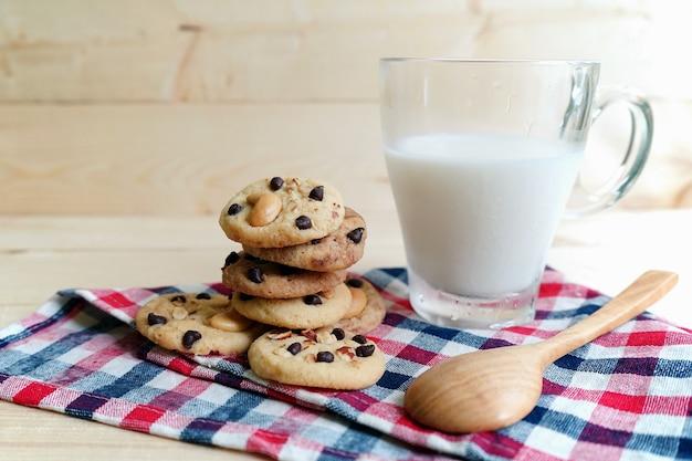 チョコレートチップクッキーと牛乳、木製の背景