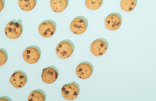 ターコイズブルーの背景にパターンで配置されたチョコレートチップクッキー。コピースペースのある甘い食べ物のコンセプト。