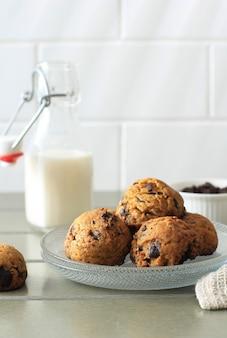 灰色の木製テーブルにコピースペースとチョコレートチップクッキーの背景。子供のためのミルクと一緒に自家製の食べ物/スナックを提供します。選択されたフォーカス