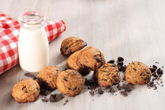 木製のテーブルにコピースペースとチョコレートチップクッキーの背景。子供向けの自家製食品/スナック、ミルク添え