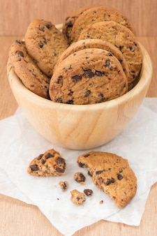Chocolate chip cookies in a bowl on wooden table.