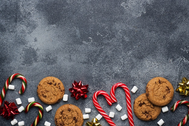 Chocolate chip cookies christmas canes caramel red gold scenery and marshmallow on dark grey . copyspace frame.