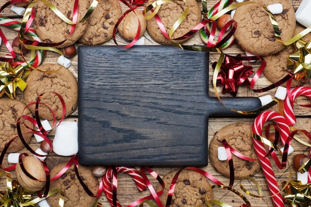 Chocolate chip cookies christmas canes caramel red gold scenery and marshmallow on wooden . copyspace frame.