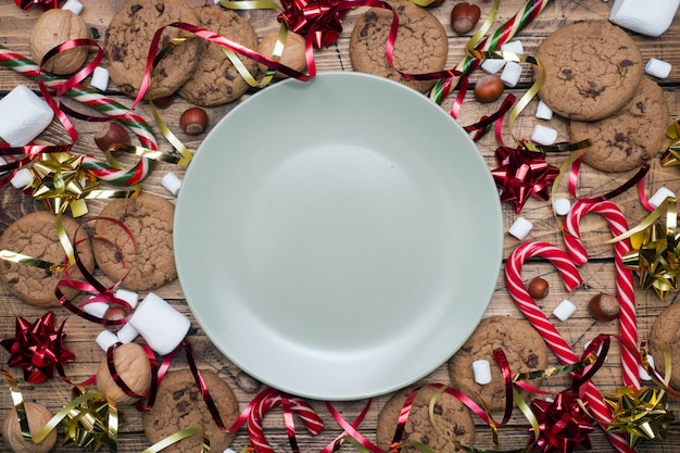Chocolate chip cookies christmas canes caramel red gold scenery and marshmallow on wooden  empty plate. copyspace frame.