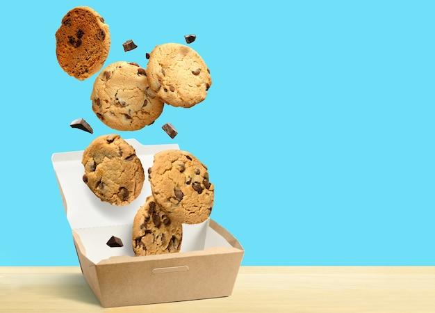 Шоколадное печенье, падающее в бумажную коробку на бирюзово-синем фоне