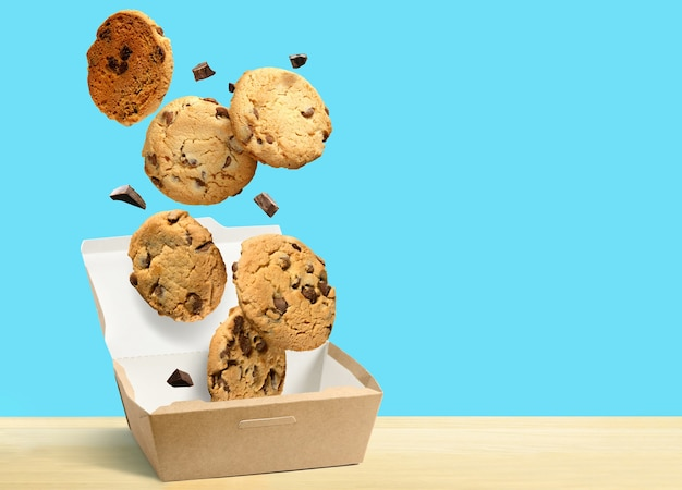Chocolate chip cookies falling in paper box over turquoise blue background