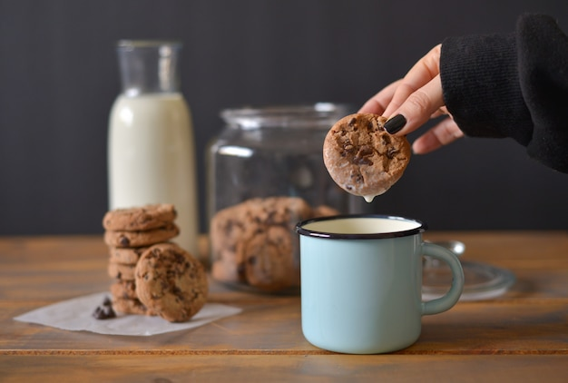 Chocolate chip cookies in glass jar with glass bottle of milk and turquoise enamel mug on wooden rustic background with women hand holding one cookie