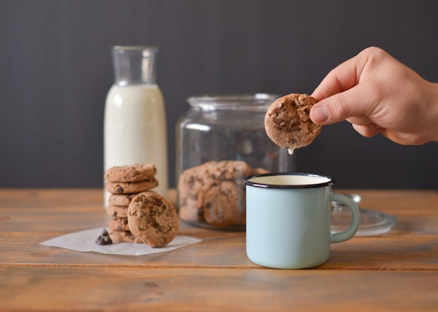 Chocolate chip cookies in glass jar with glass bottle of milk and turquoise enamel mug on wooden rustic table with men hand holding one cookie