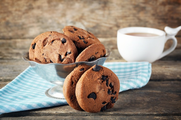 나무 테이블에 있는 금속 그릇에 초콜릿 칩 쿠키