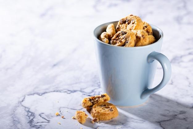 大理石の石の表面に青いカップのチョコレートチップクッキー。セレクティブフォーカス。コピースペース