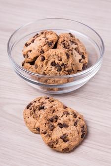 木製のテーブルの背景にガラスのボウルにチョコレートチップクッキー