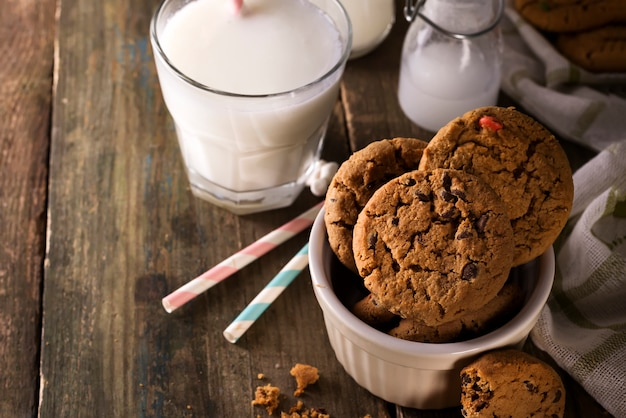 Chocolate chip cookies and milk on a rustic wood background