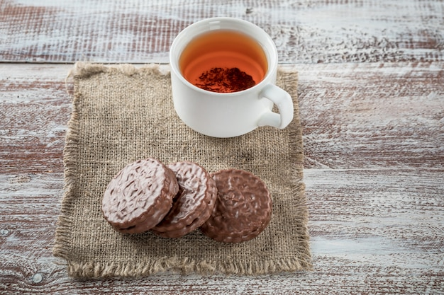 Chocolate chip cookies and a mug of tea on white wooden table.