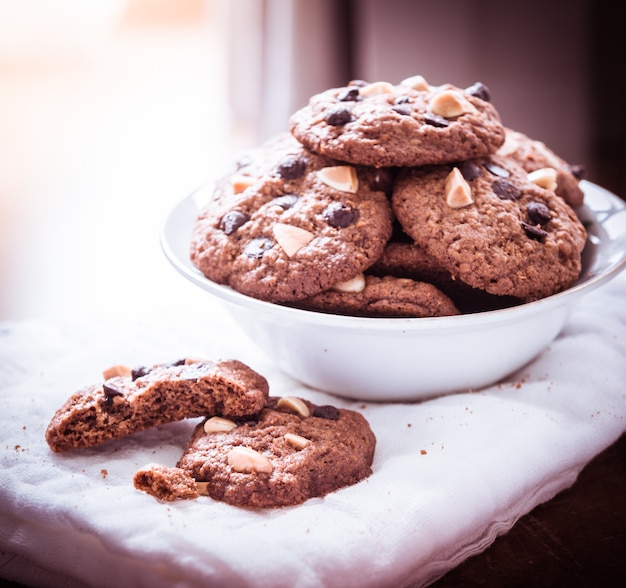 Chocolate chip cookies on napkin on wooden table.