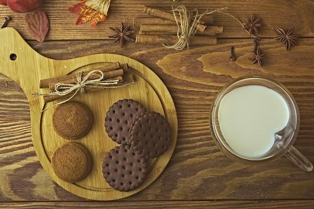 Шоколадное печенье на подносе и молоко в кружке для выпечки с палочками корицы на деревянном фоне ...