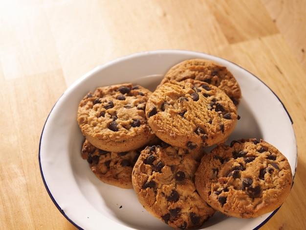 나무 테이블에 초콜릿 칩 쿠키 나무 테이블에 백랍 접시에 초콜릿 칩 쿠키
