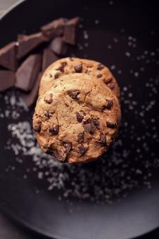 黒いプレートにチョコレートチップクッキー。暗い古い木製のテーブル。