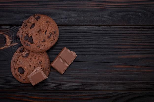 暗い古い木製のテーブルにチョコレートチップクッキー