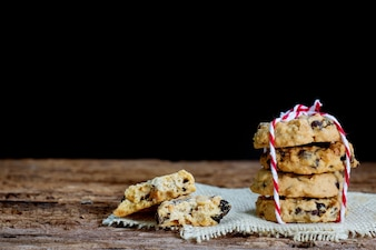 Chocolate chip cookies on napkin with dark background.