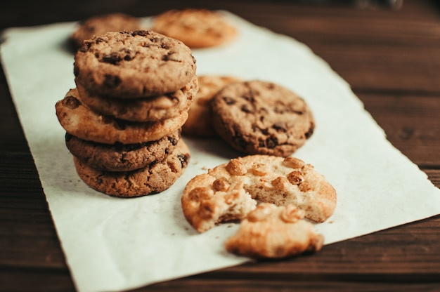 Chocolate chip cookies and one broken cookie on wooden background