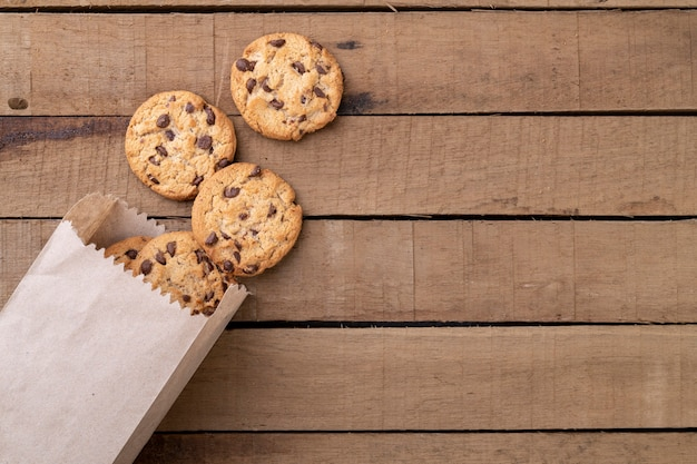 Chocolate chip cookies on a paper bag over a wooden table with copy space.