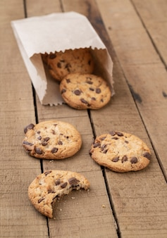 Chocolate chip cookies on a paper bag over a wooden table.
