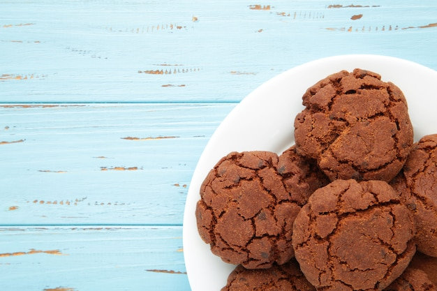 Chocolate chip cookies on a plate on blue background.