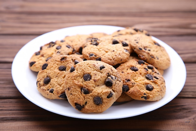 Chocolate chip cookies on plate on brown wooden background