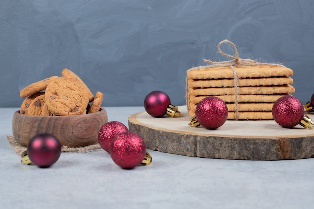 Chocolate chip cookies, stack of biscuits and christmas balls on marble table. high quality photo