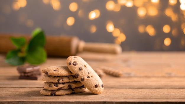 木製のテーブルに積み上げられたチョコレートチップクッキー、麺棒と緑の枝