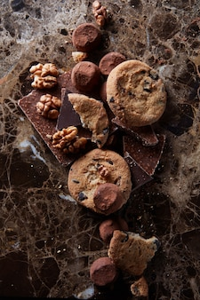 暗い大理石の表面にチョコレート菓子が入ったチョコレートチップクッキー。