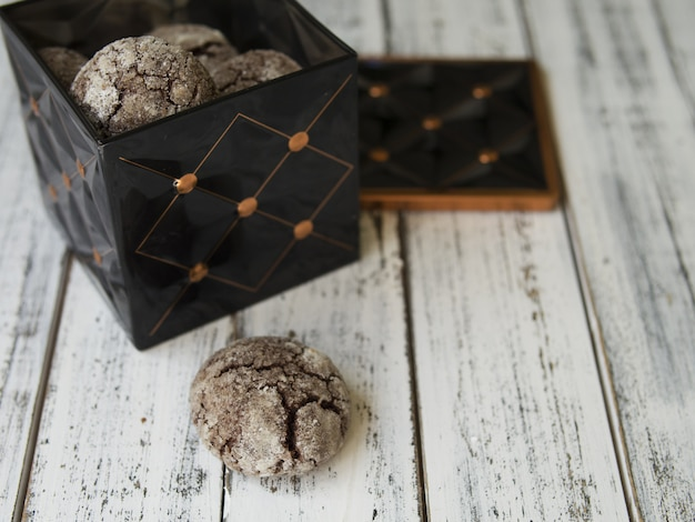 Chocolate chip cookies with cracks, black vintage box with cookies on white background.