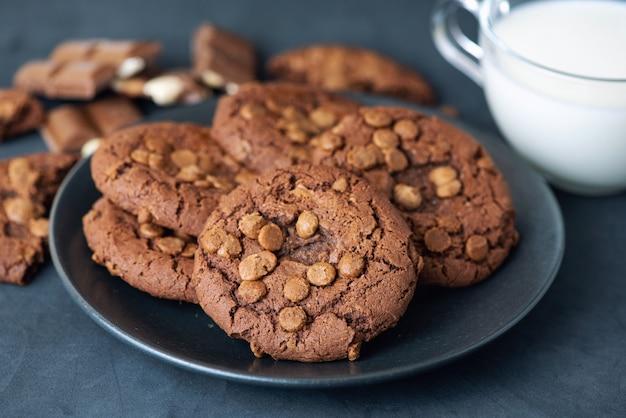 ダークテーブルの上のミルクのカップとチョコレートチップクッキー。閉じる