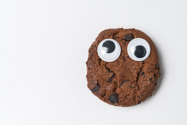 Chocolate chip cookies with googly eyes on white wall. cookies with funny face