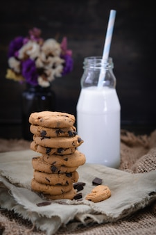 Chocolate chip cookies with milk on rustic wooden table.