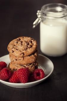 素朴な木の背景に赤いラズベリーとミルクとチョコレートチップクッキー。自家製デザート。
