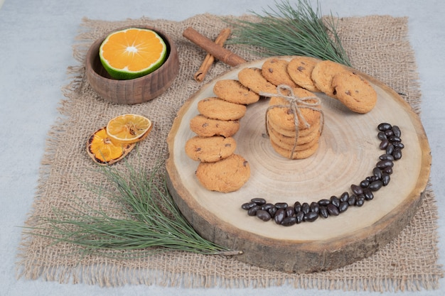 Chocolate chip cookies on wooden board with cinnamon and slices of tangerine. high quality photo