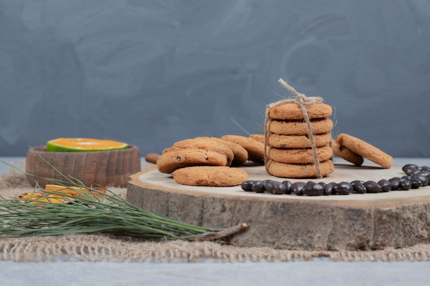 Chocolate chip cookies on wooden board with grains and slices of tangerine. high quality photo