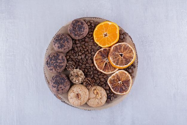 Покрытые шоколадной стружкой печенье, кофейные зерна и дольки апельсина на доске на белом фоне.